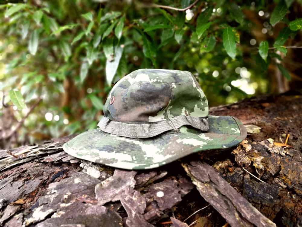 A close look at a camouflage print boonie hat on a tree trunk.