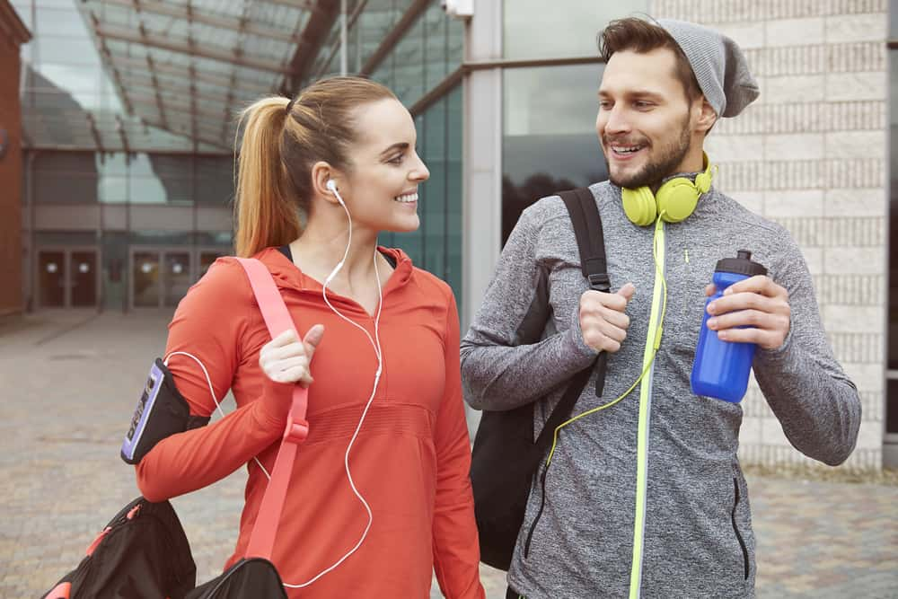 A couple wearing workout clothes on their way home from the gym.