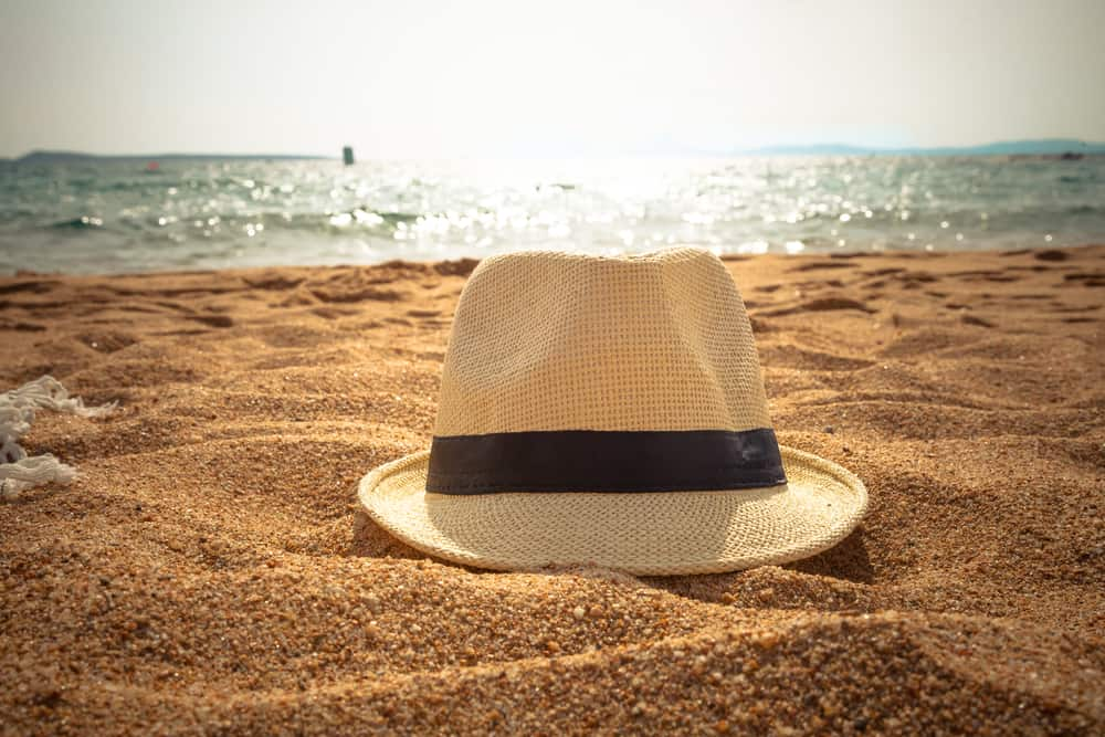 This is a close look at a fedora on a sandy beach.