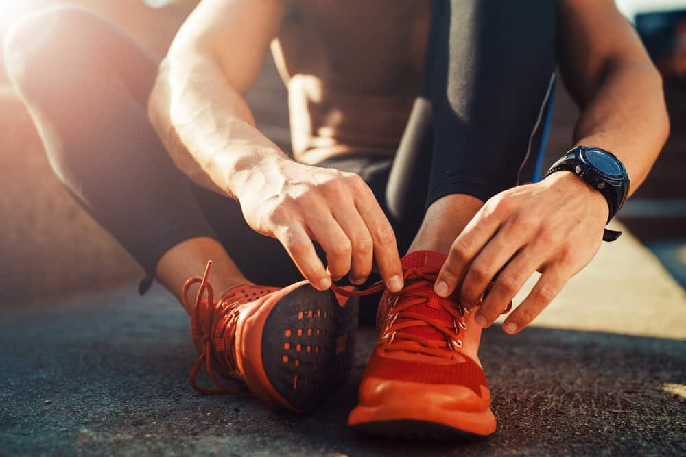 This is a close look at a jogger putting on his red running shoes.