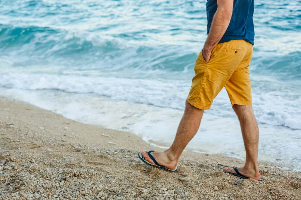 A close look at a man wearing a pair of shorts while walking on the beach.