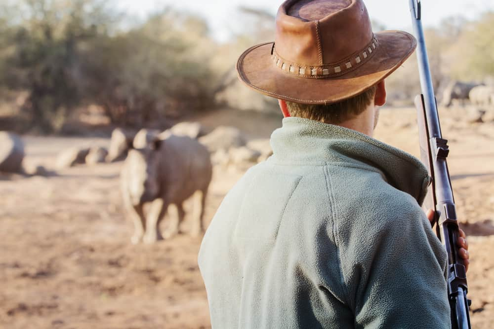A man wearing a brown campaign hat in an animal preserve.