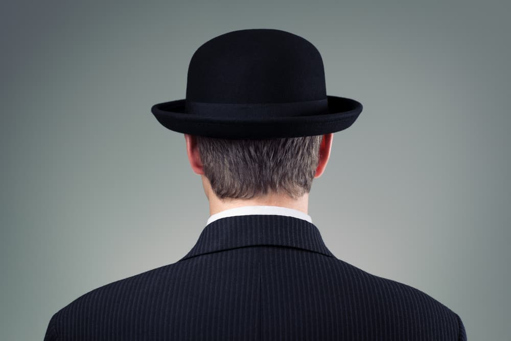 A back view of a man wearing a dark suit and a bowler hat.