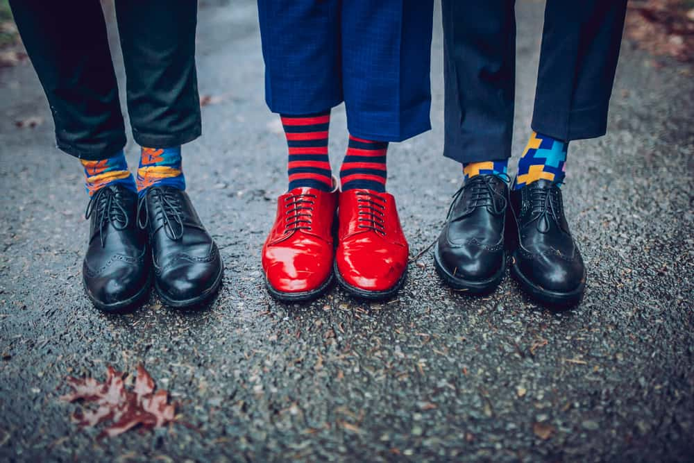 A row of men wearing colorful patterned socks.