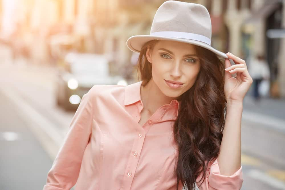 A woman wearing a pink blouse with her light gray fedora.