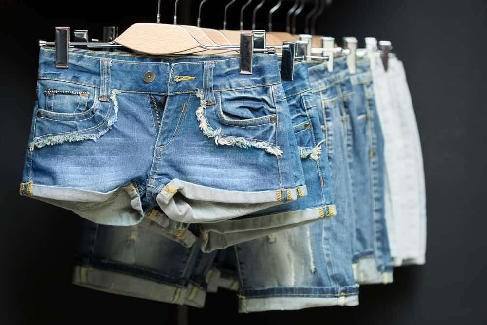A row of shorts on a rack display at a store.