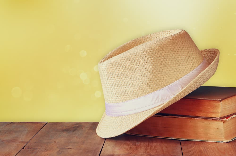 This is a straw woven fedora on a wooden table.