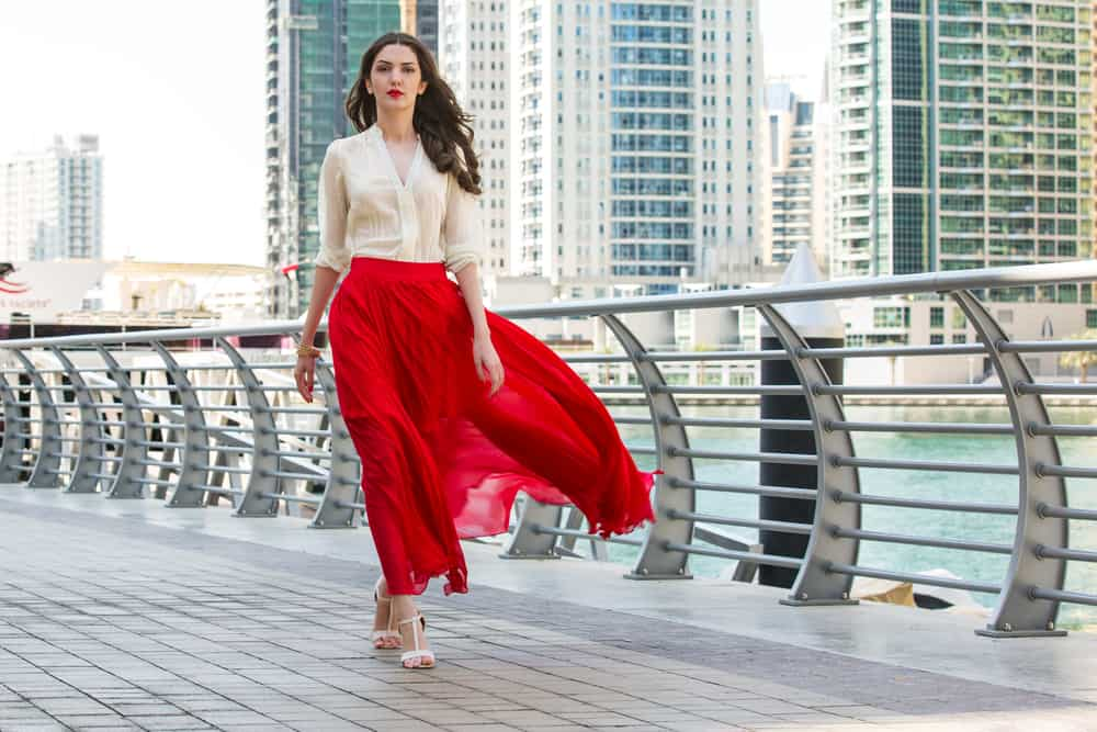 A woman wearing red skirt by the bay.