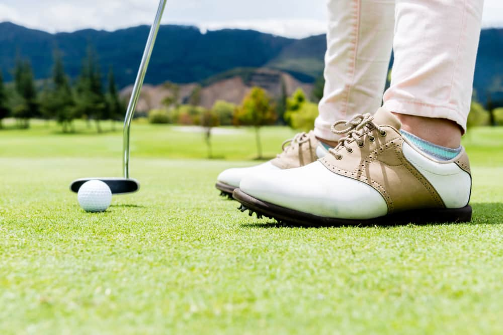 A golfer wearing a pair of golf shoes.
