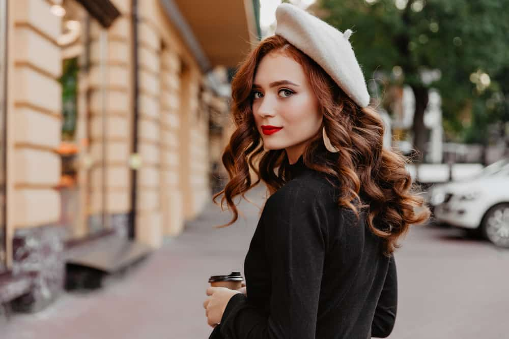 A woman wearing a beret while walking on the sidewalk.
