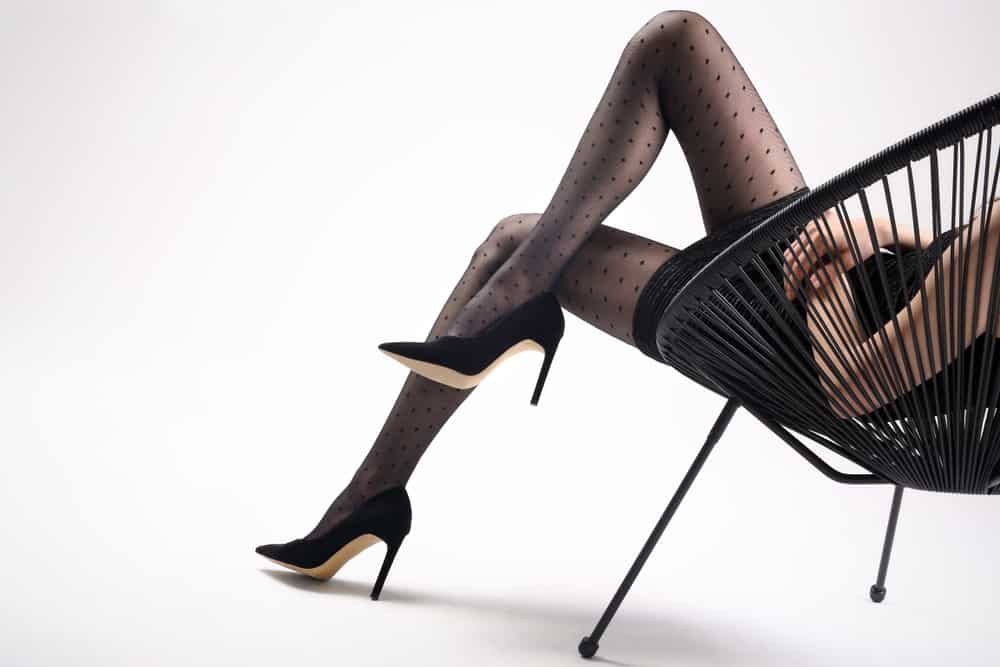 A woman wearing a little black dress, black patterned tights and black stilettos.