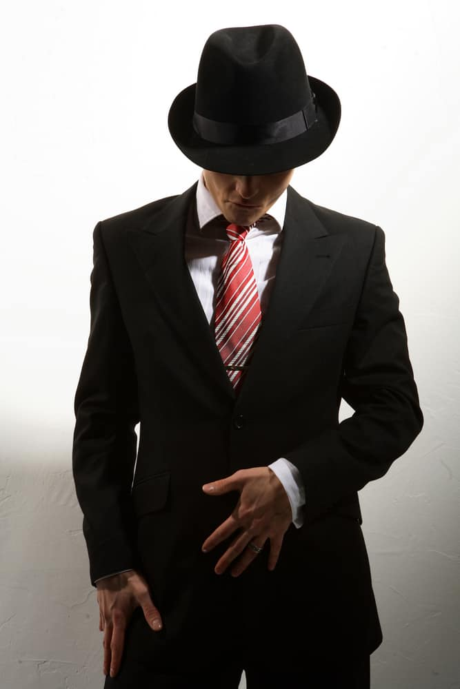 A man wearing a black fedora with his black suit.
