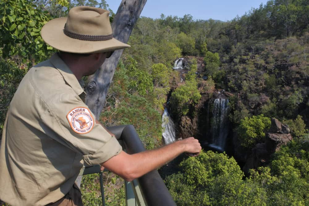A park ranger looking over the waterfalls in the distance.