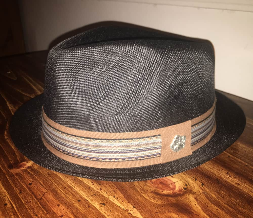 This is a close look at a pork pie hat on a table.