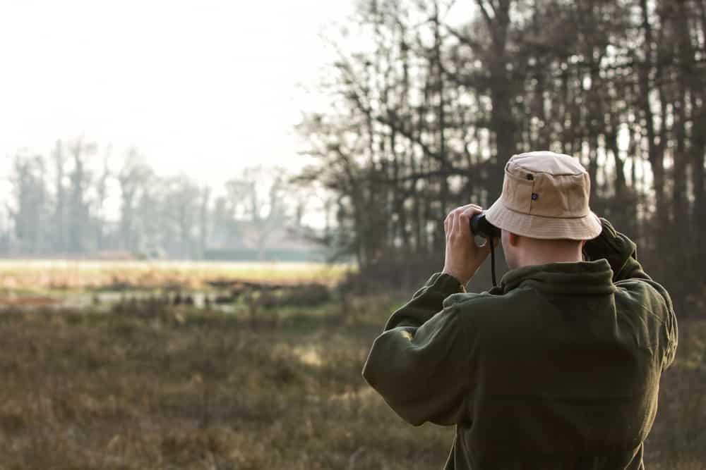 A bird watcher wearing a hat and a coat using his binoculars.