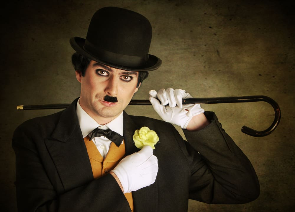 This is a close look at a man dressed as Charlie Chaplin.