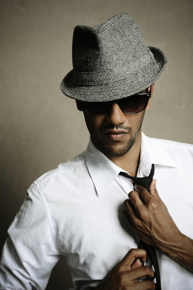 A man wearing a gray fedora with his white button-down shirt and tie.