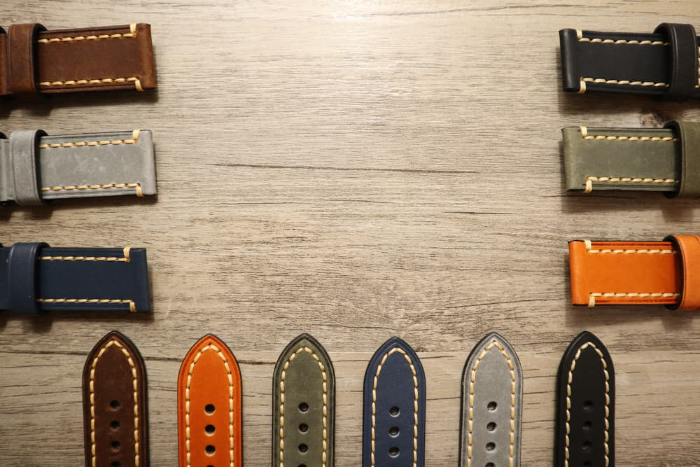 This is a close look at various colorful watch straps on a wooden table.