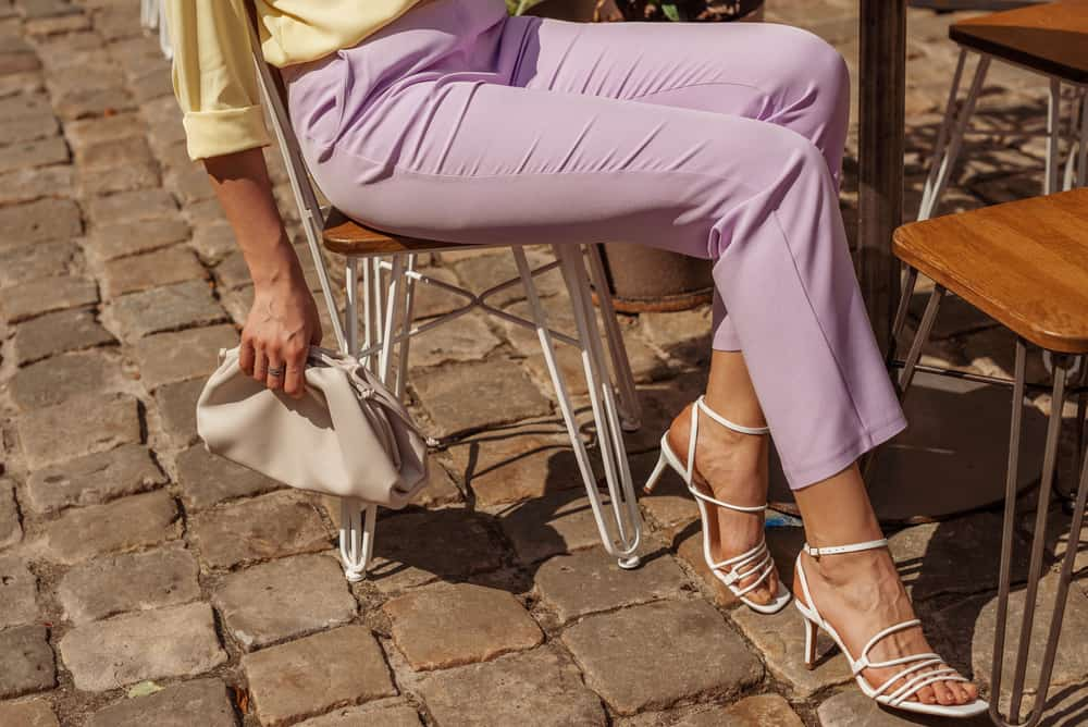 This is a close look at a woman wearing a pair of lilac trousers.