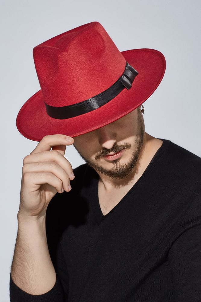 A man wearing a black shirt and red fedora.