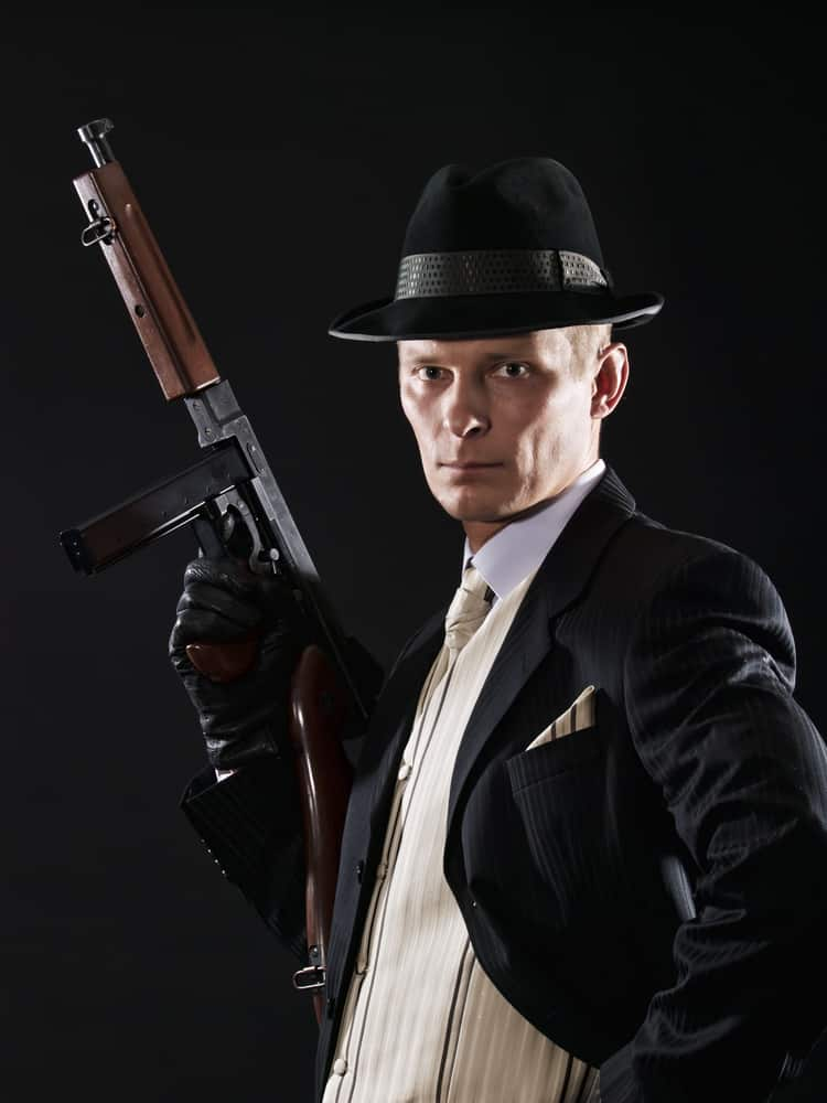 A man in a gangster costume with a fedora.