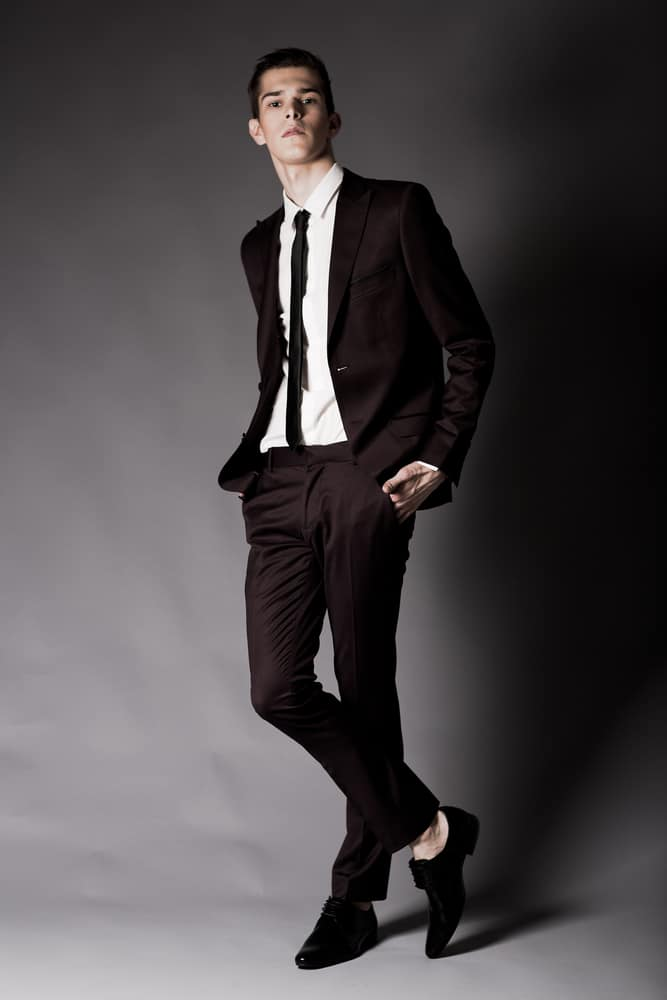 A man wearing a black suit with dress pants.