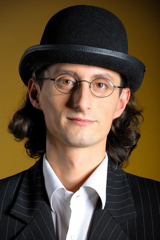 A man wearing a pin-striped suit and a bowler hat.