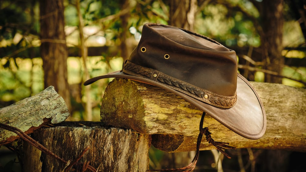 A brown leather outback hat on a log fence post.