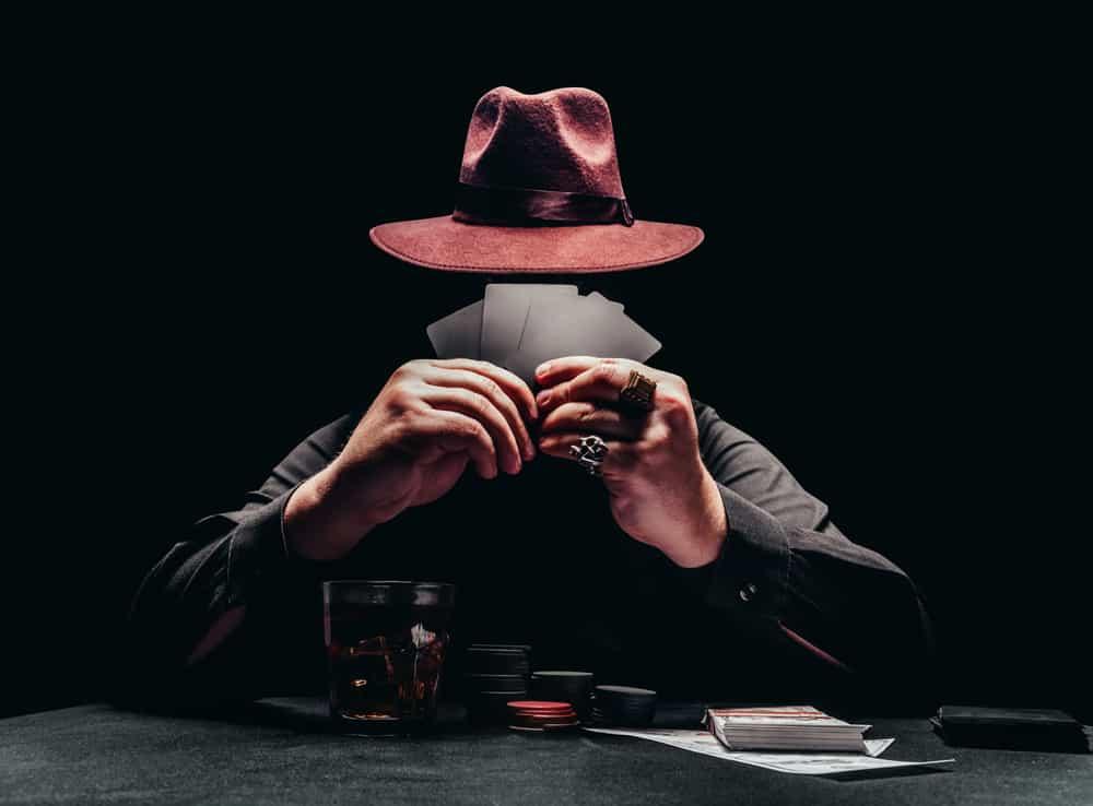 A gambler wearing a gambler hat while gambling.
