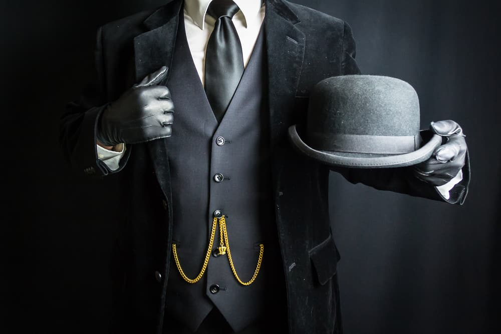 This is a man wearing a dark suit and a bowler hat in hand.