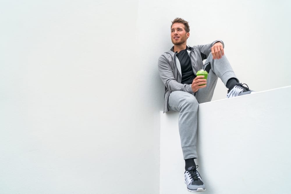 A man wearing exercise clothes with sweatpants.