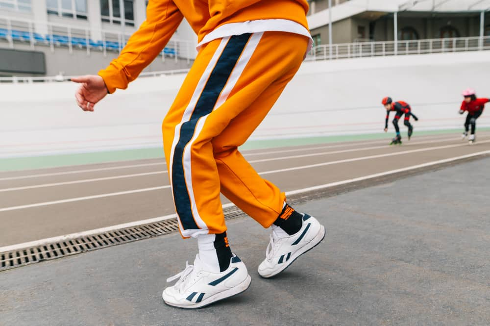 A man wearing a pair of yellow track pants.