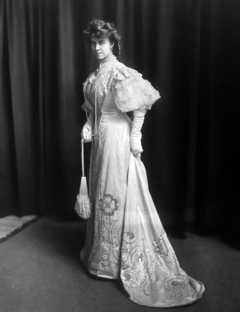 Woman wearing an 1890s wedding dress paired with layered necklace and a purse.