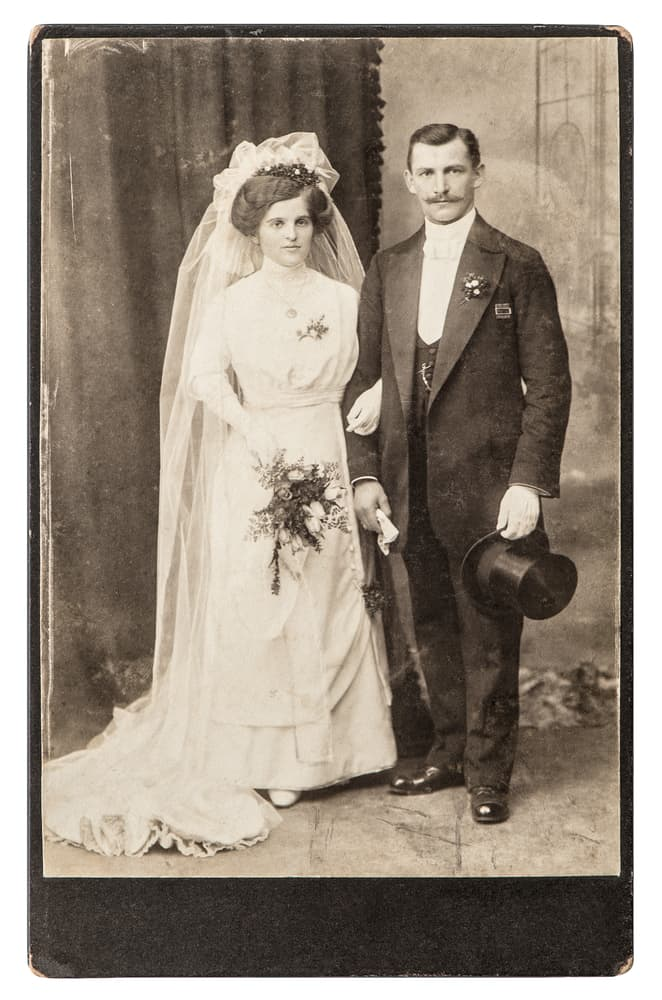 Antique portrait of a married couple in white wedding dress and black suit.