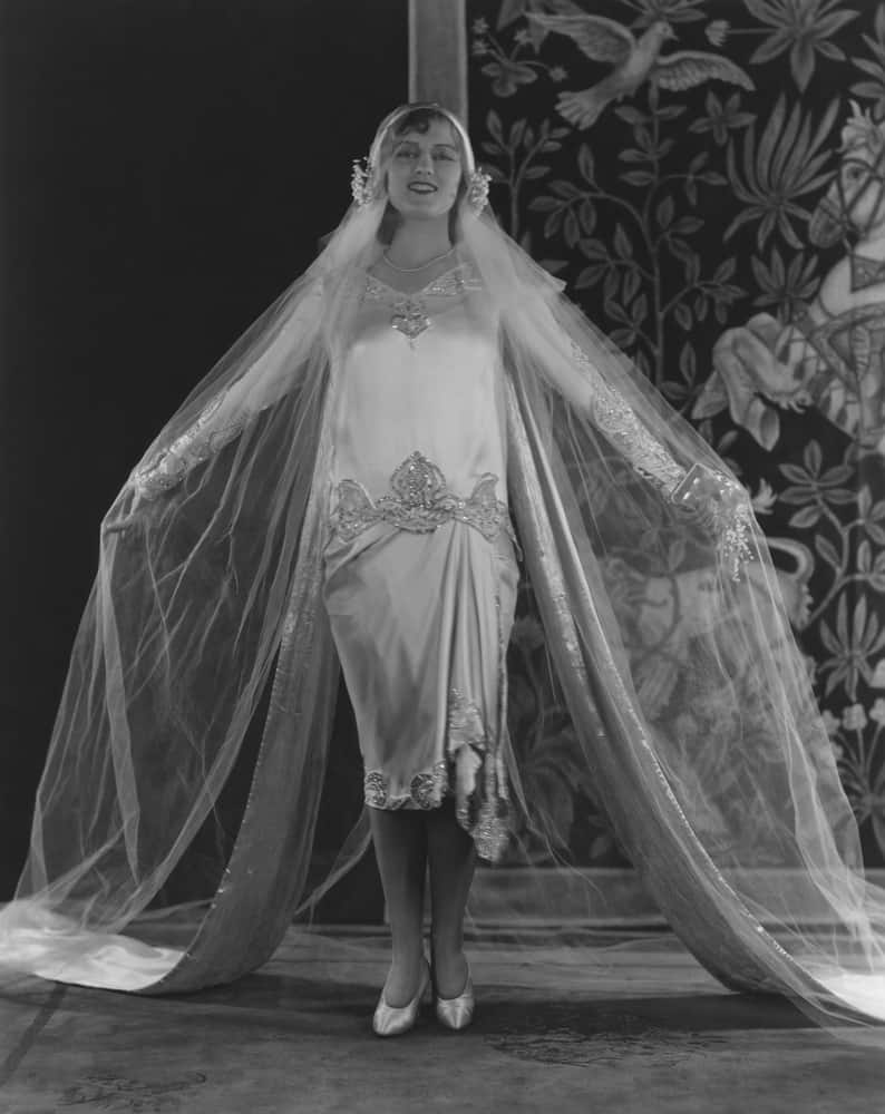 Black and white photo of a young bride in a loose wedding gown.