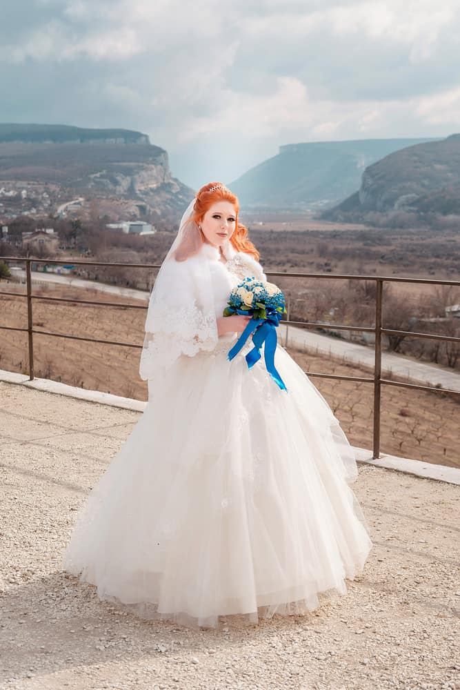Red-haired bride in a large, princess-style gown holding a blue bouquet.