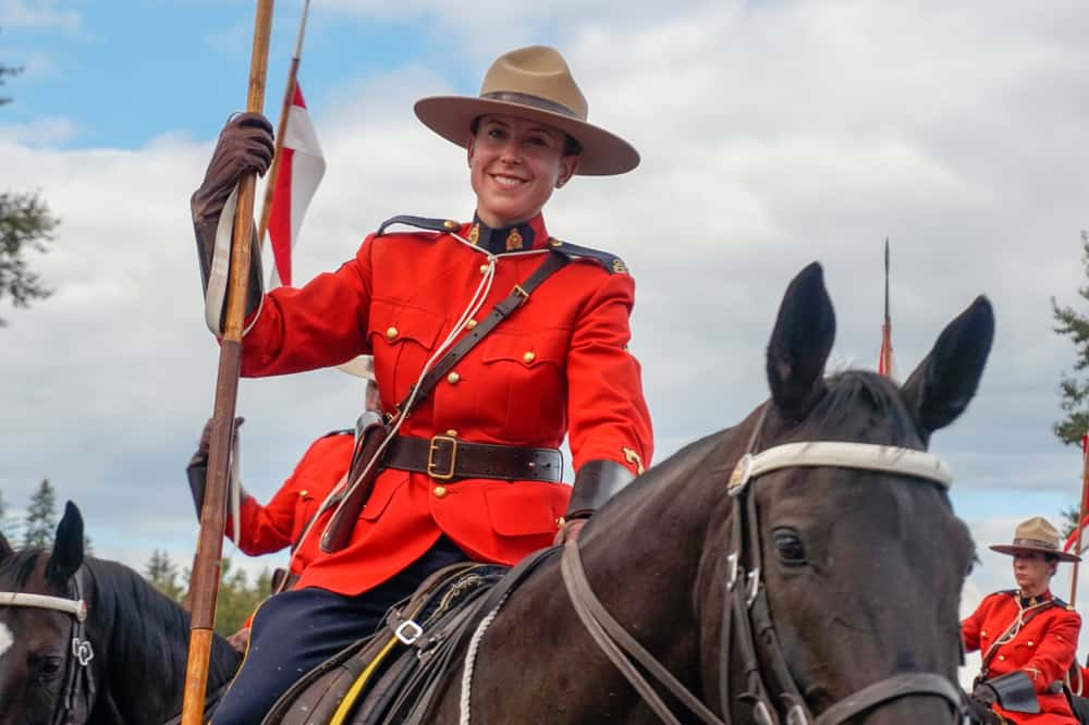 A Canadian Ranger atop a large brown horse.