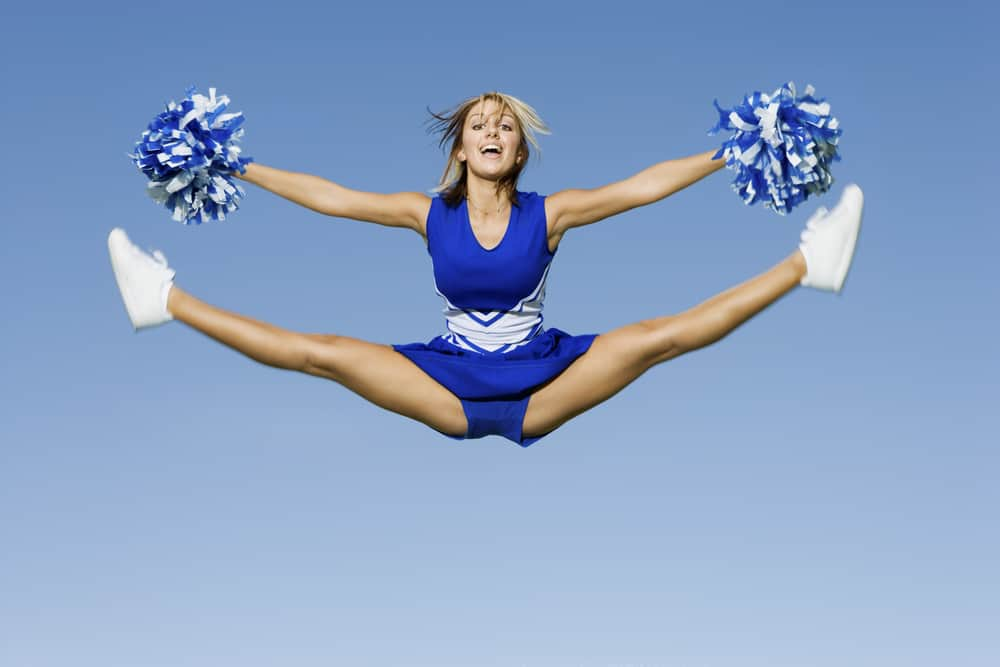 A cheerleader doing an aerial stunt while wearing a skirt.