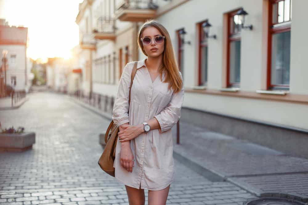 This is a woman wearing a beige button down dress shirt.
