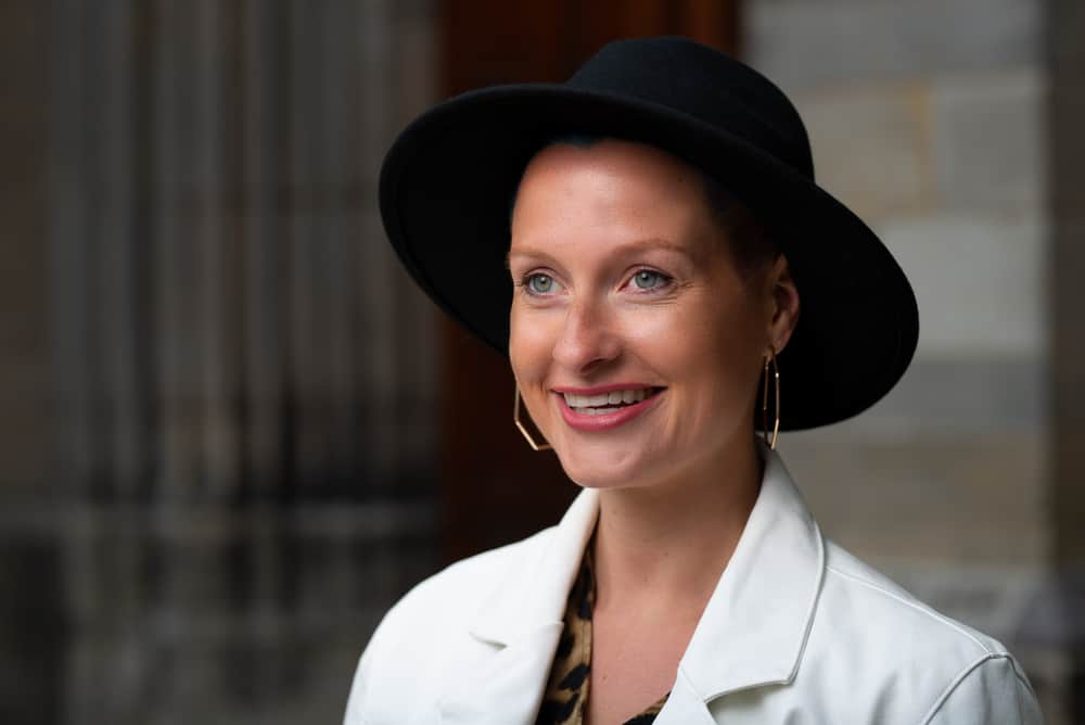A woman wearing a black fedora with her white coat.