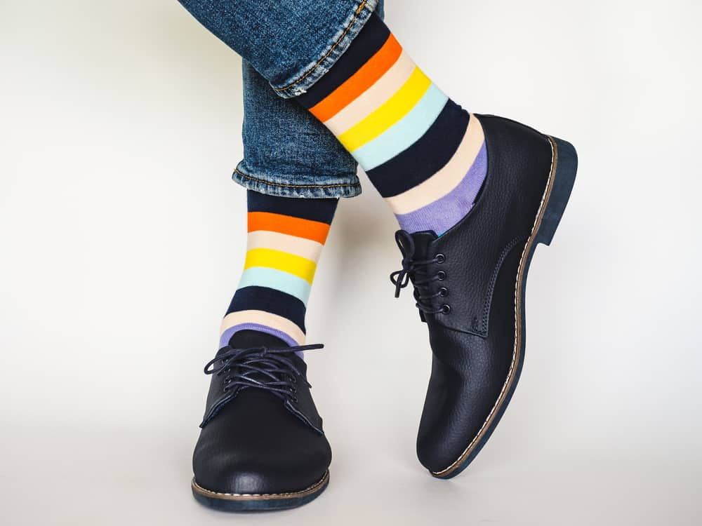 A close look at a pair of colorful striped socks paired with black leather shoes.