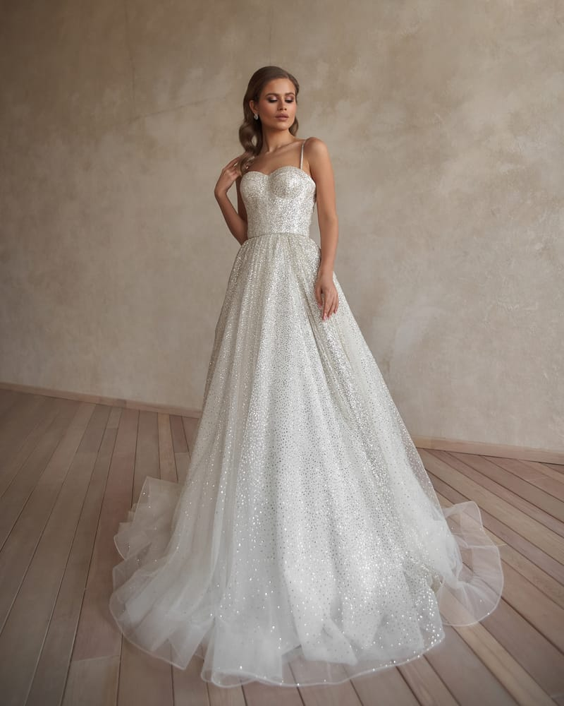 Bride in a beaded wedding gown poses against the concrete wall.