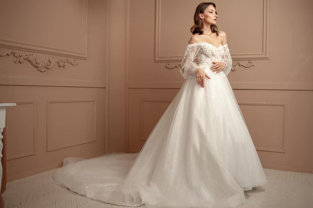 Bride in an off-shoulder wedding dress poses against the intricate wainscoted walls.