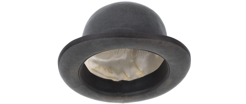 A close look at a charcoal gray bowler hat with silk lining inside.
