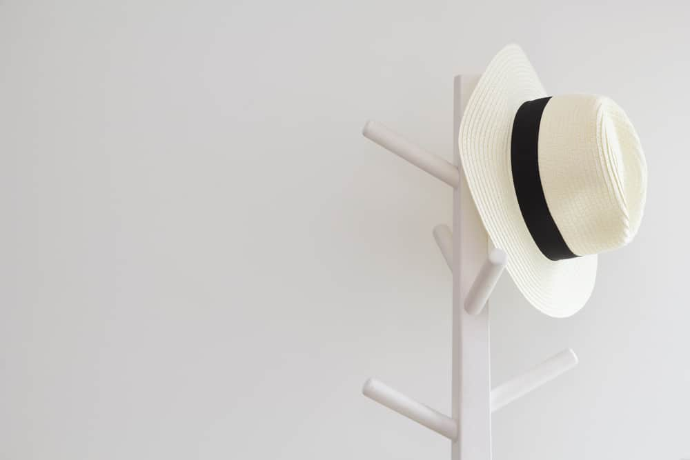 A white fedora hanging on a hat rack.