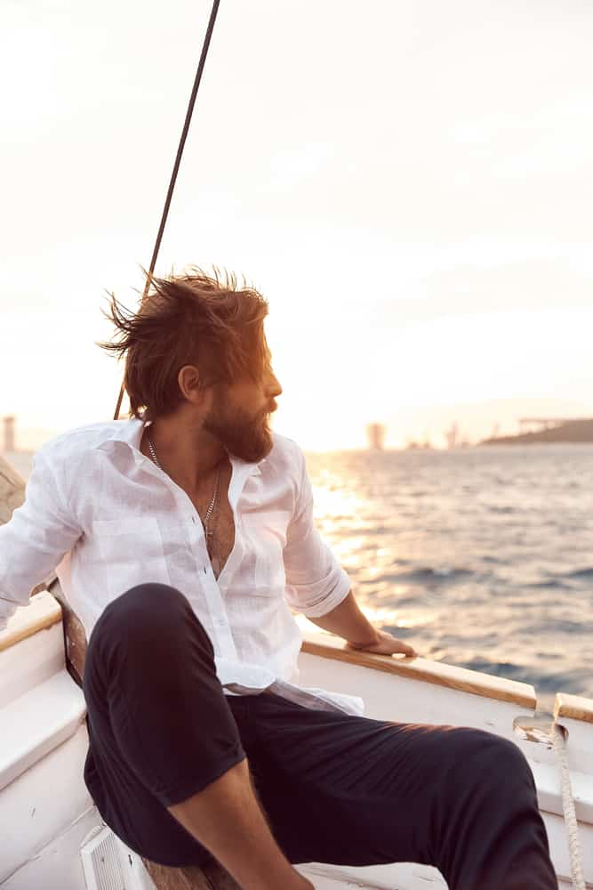 A man on yacht wearing a white linen shirt and blue pants.