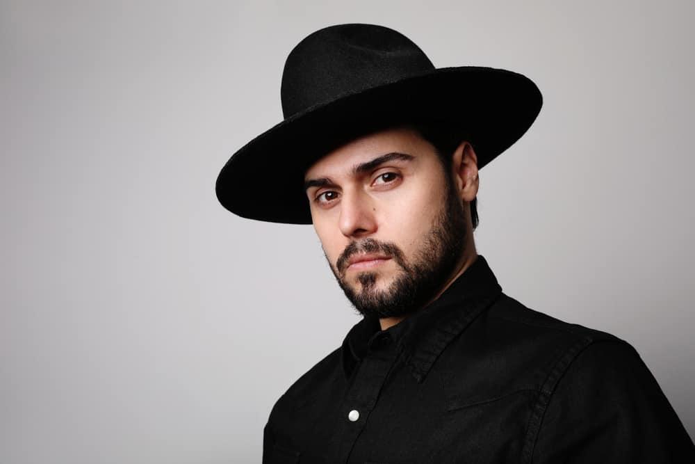 A man wearing a wide brim black fedora.
