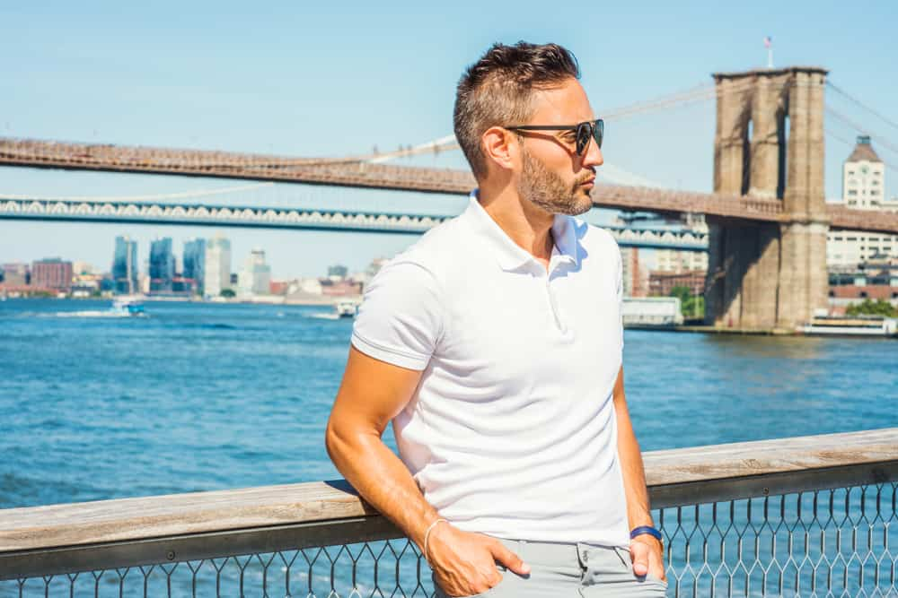 This is a man wearing a white polo shirt by the water.