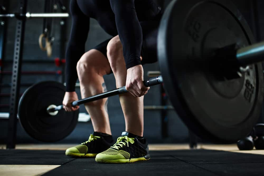 This is a close look at a weightlifter wearing cross training shoes.