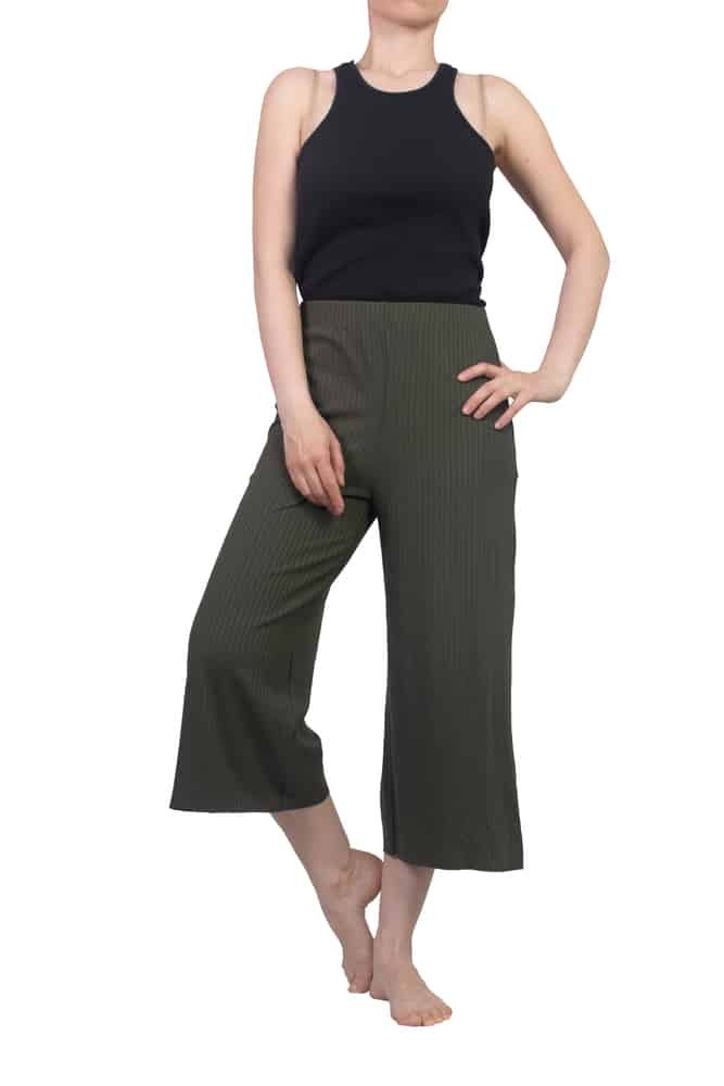 A woman wearing a pair of green capri pants.